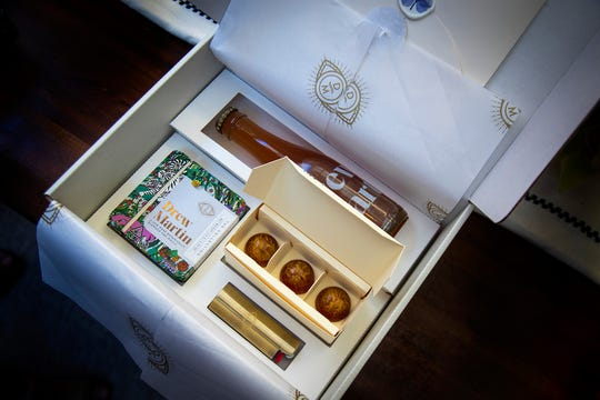 The day of the virtual salon, each invitee receives a decorative box containing a themed bottled cocktail, clockwise from left, a dessert, a lighter and a variety four-pack of pre-rolled Drew Martin joints.