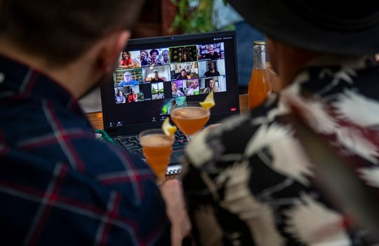 A pair of rose sour cocktails created by herbalist and mixologist Drew Martin Gosselin, front, and a computer screen filled with the participants of the virtual salon, rear, on June 25, 2020 in Los Angeles, California.